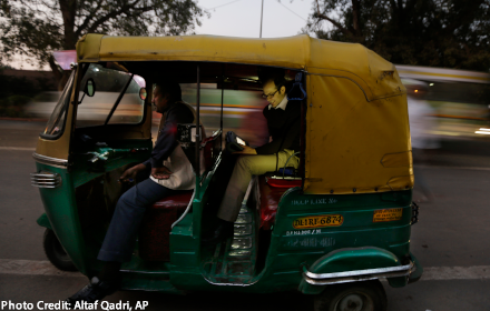 Prof. Joshua Apte in the back of an auto-rickshaw, seen from outside the vehicle