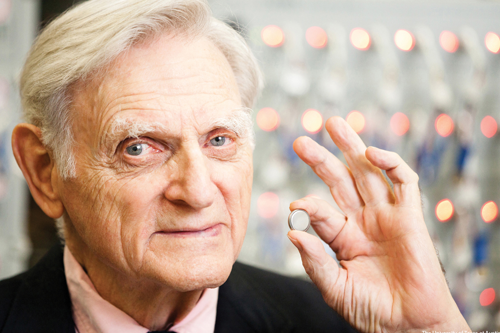 John Goodenough holds a coin cell battery between his index finger and thumb