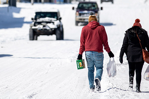 two people walk through snow carrying groceries as vehicles approach in the other direction
