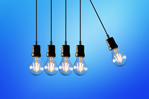 One light bulb swings toward four stationary light bulbs on a blue background