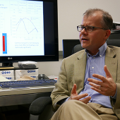 Professor Erich Schneider being interviewed at his desk