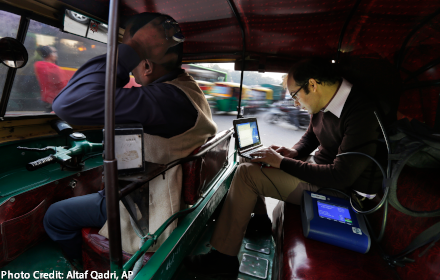 Prof. Joshua Apte works on a laptop in the back of an auto-rickshaw
