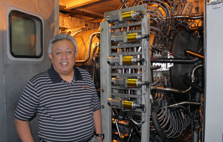 Juan Ontiveros stands in front of power plant equipment